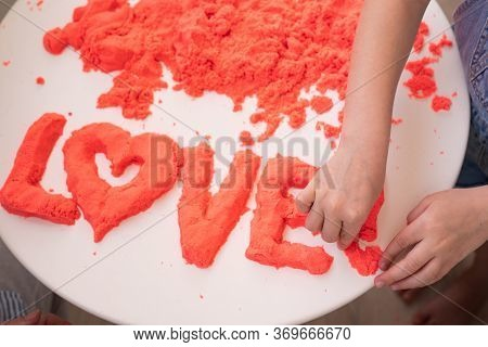 Hand Molded Of Red Kinetic Sand The Word Love. The Development Of Fine Motor Skills. Educational Gam