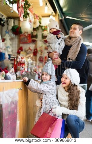 Smiling Parents With Kids At Counter Of X-mas Market. Shallow Depth Of Focus Only On Woman With Chil