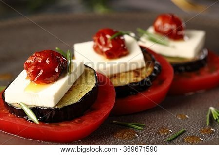 Appetizer Of Ripe Tomatoes, Feta Cheese, Fried Eggplant, Sun Dried Tomatoes In Oil And Rosemary Leav
