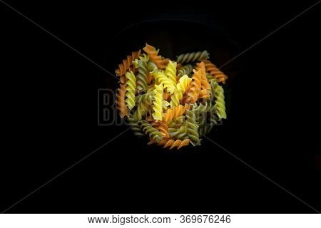 Composition Of Raw Pasta Uncooked Tricolor Fusilli, Pasta Twist Shape. Close Up And Selective Focus