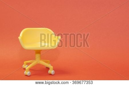 Concept Of Vacant Chair. Yellow Stool On Orange Clean Background. Photo In Minimal Style.