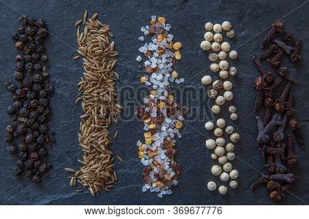 Rows Of Various Aromatic Spices On A Black Slate Background, Top View. A Set Of Spices. Food And Kit