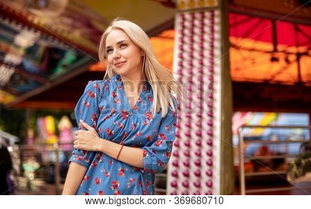 Alluring Millennial Blond Girl In Casual Dress Looking Away And Smiling Against Blurred Vibrant Mult