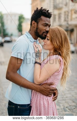 Interracial Relations. An African Man And A Caucasian Woman Stand Embracing On A City Street.