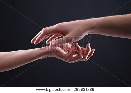 A Close-up Of Two Hands Male And Female On A Black Background Gently Touch Each Other. Confidence In