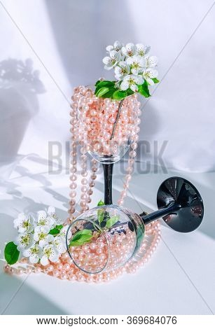 Beautiful Blooming Pear Tree Branch With White Flowers In Wine Glass With Pink Pearl Beads.