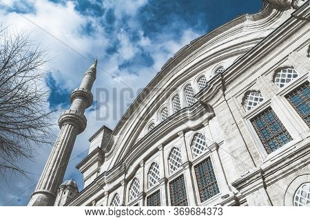 Beautiful Minaret Of White Stone On A Background Of Blue Sky With Clouds. Minaret Against The Sky Wi