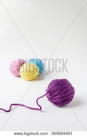 Close Up Of Violet Woolen Ball. Three Other Woolen Balls In Background On Light Backdrop.