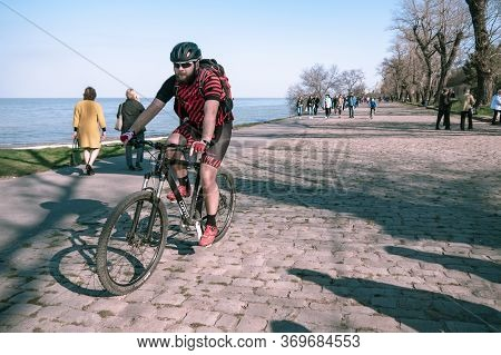 Taganrog, Russia - 07.04.19: Professional Cycled Pedal Rides Among The People On The Stone Pavement.