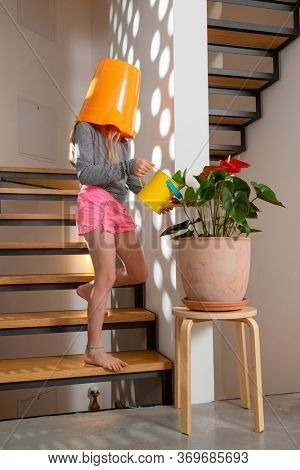 Little girl with bucket on her head takes care of the flowers of her home, the staircase is in wood.