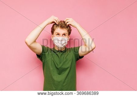 Portrait Of A Shaggy Young Blond Man With A Dissatisfied Face In A Medical Mask Touches His Regrown