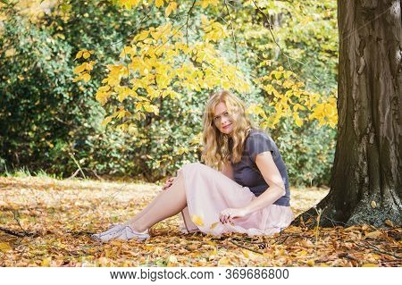 Young Woman Sit Under Tree In Autumn City Park. Daydreaming Mood