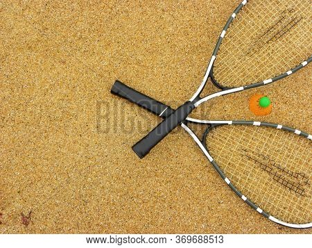 Badminton Concept. Badminton Rackets And Shuttlecock On Sand Background. Top View Of Space For Text.
