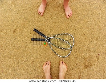 Badminton Concept. Badminton Rackets, Shuttlecock And Male And Female Feet On Sand Background. Top V