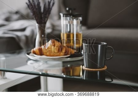Herbal Tea In A Black Mug And Croissant Served On A Glass Coffee Table In Living Room