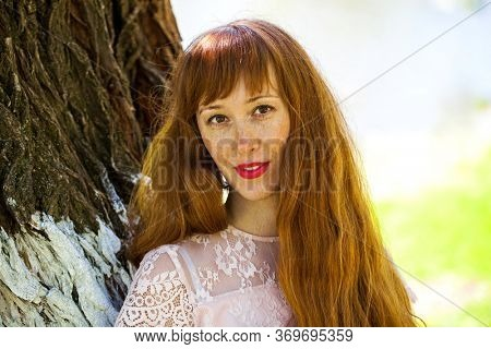 Portrait of a young beautiful redhair woman on the background of tree bark