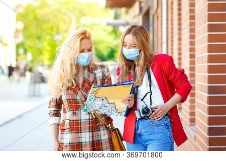Stylish Girls Looking Into Tourist Map In The City. Tourists Girls Are Exploring New City Together.