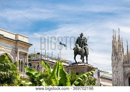 Milan. Italy - May 21, 2019: Vittorio Emanuele II Statue in Milan on Piazza Duomo. Palm Trees on Foreground.