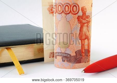 Black Daily Planner, Red Pen And A Banknote 5000 Rubles. Banknote Folded Into A Tube And Stands Upri
