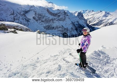 Teen Girl Skier Stand On The Top Of The Mountain On In Snow Wearing Ski Turn And Look At Camera