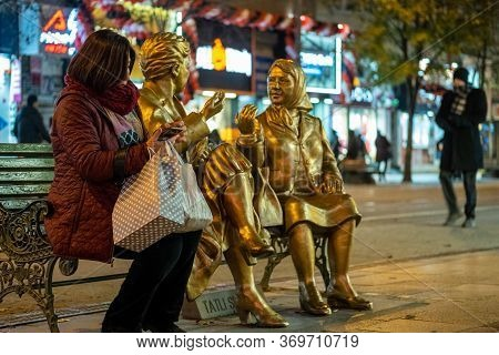 Eskisehir, Turkey - December 07, 2019: Woman Sitting On A Bench Near Two Golden Women Sculptures At