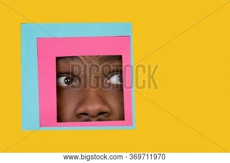Scared. Face Of Emotional African-american Man Peeks Throught Square In Yellow Background. Trendy Ge