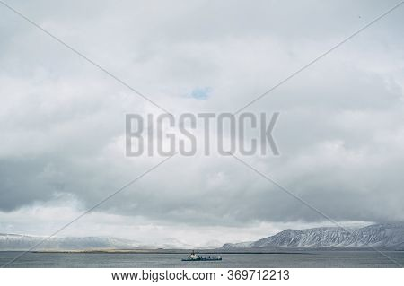 The Barge Sails On The Atlantic Ocean, Near Iceland, Against The Backdrop Of Snow-capped Mountains.