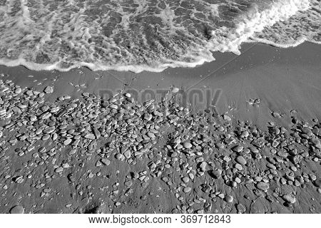 Small Stones Sand And Sea Wave In Black And White. Seasonal Natural Background.