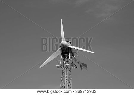 Old Wind Turbine Against Blue Sky. Background And View