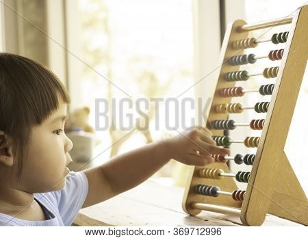 Lovely Little Girl Learning With Educational Colorful Wooden Abacus And Counting Indoors. Home Schoo
