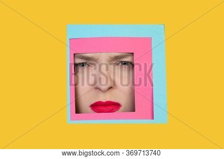 Angry. Face Of Emotional Caucasian Woman Peeks Throught Square In Yellow Background. Trendy Geometri