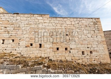 Closeup Of An Austrian Fortified Wall Made Of Irregular Stone Blocks With Arrowslits Or Loopholes