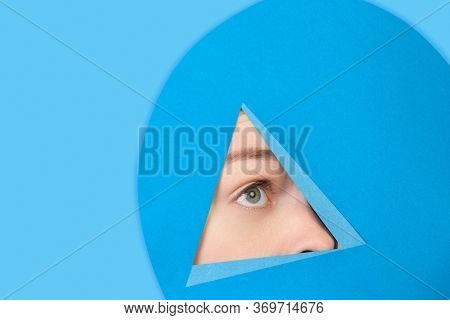 Hopeful. Face Of Emotional Caucasian Woman Peeks Throught Triangle In Blue Background. Trendy Geomet