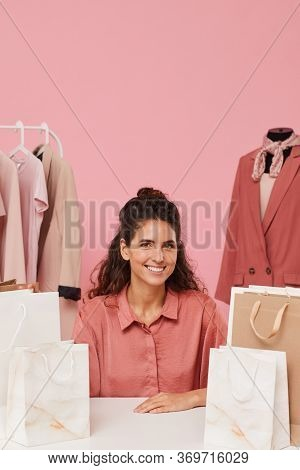 Portrait Of Young Woman Sitting At The Table Among Paper Bags And Smiling At Camera With Clothes On
