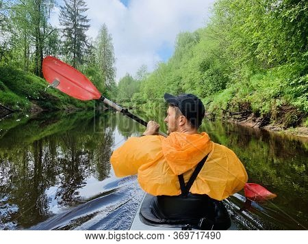 Russia, Kirishi, 25 May 2019: The Men In A Cap And Raincoat Of Orange Color Floats On A Kayak On The