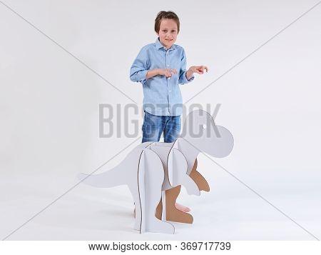 Little Dreamer Boy Playing With A Cardboard Dinosaur Tyrannosaurus Rex. Childhood. Fantasy, Imaginat
