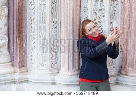 Selfie. Closeup Portrait Head Shot Young Redhead Woman In Black Coat, Red Scarf Taking Herself A Pho