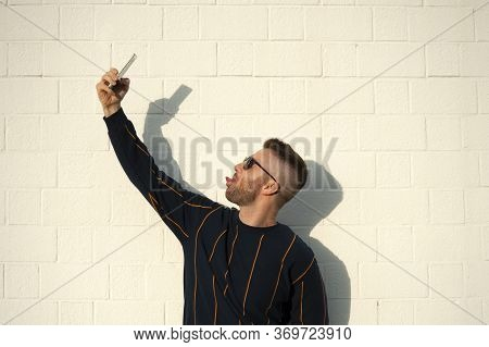 Positive Smiling Guy In Casualwear Showing Tongue With Mobile Phone Taking Selfie. Young Bearded Man
