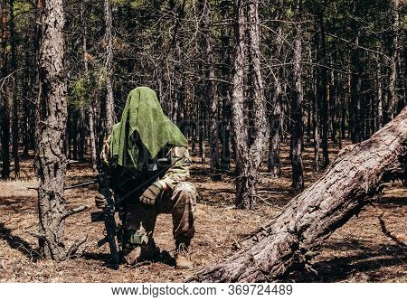 Photo Of A Fully Equipped Camouflaged Forest Sniper With Rifle And Tactical Net Scarf Sitting In Woo