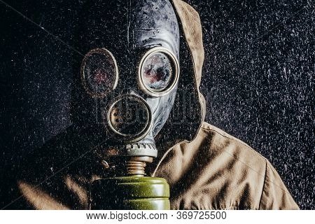 Photo Of A Stalker Face In Soviet Gas Mask In Rain On Black Background.