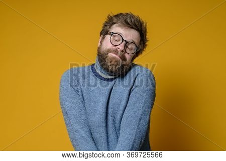 Shy Caucasian Man With A Shaggy Hairstyle And Beard Modestly Folded Hands And Closed Eyes, With A Cu