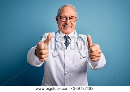 Senior grey haired doctor man wearing stethoscope and medical coat over blue background approving doing positive gesture with hand, thumbs up smiling and happy for success. Winner gesture.