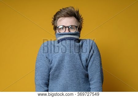 Shy, Scared Caucasian Shaggy Man Hiding Behind His Knitted Sweater And Looks Uncertainly At The Came