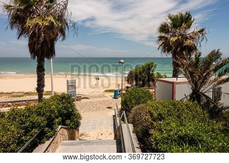 Mil Palmeras, Valenciana, Spain - June 03 2020 : People Observing Social Distancing On Beach, Due To