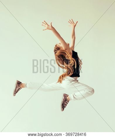 Excited young girl leaping in the air with her hands raised. Sport, training, dancing lifestyle.