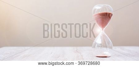 Hourglass On Table, Sand Flowing Through The Bulb Of Sandglass Measuring The Passing Time. Countdown