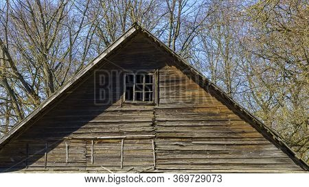 Pediment With Small Window Of An Abandoned Rustic House On A Branches Trees Background. Countryside