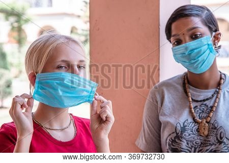 Portrait Of Two Caucasian And African Girls In Protective Masks, Coronavirus Concept. Teen Girl Remo