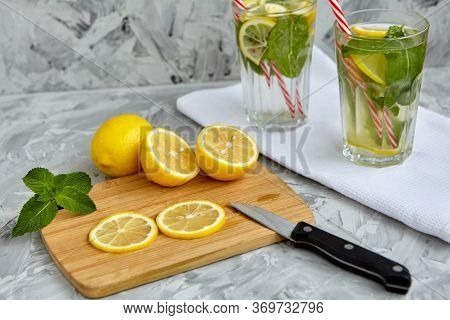 The Process Of Making Lemonade. On A Wooden Board Is A Lemon And Mint Next To A Knife. There Are Gla
