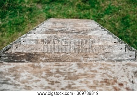 Old Wooden Stairs Going Down On A Background Of Green Grass. Top View. Copy, Empty Space For Text